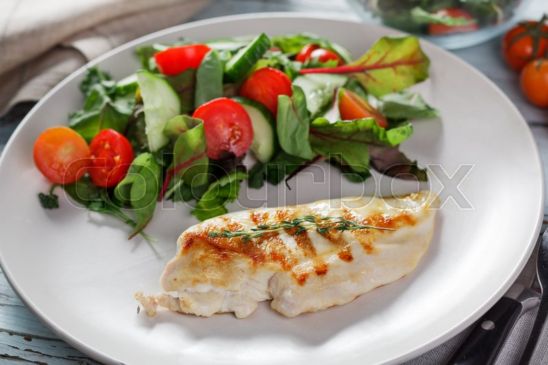 Stock image of 'Grilled chicken meat with fresh vegetable salad, tomatoes on white plate'
