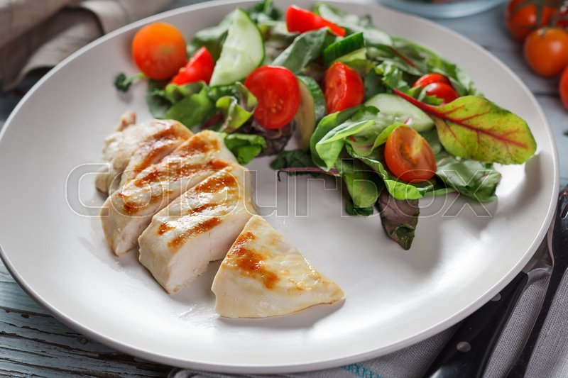Stock image of 'Cutted grilled chicken meat with fresh vegetable salad, tomatoes on white plate'