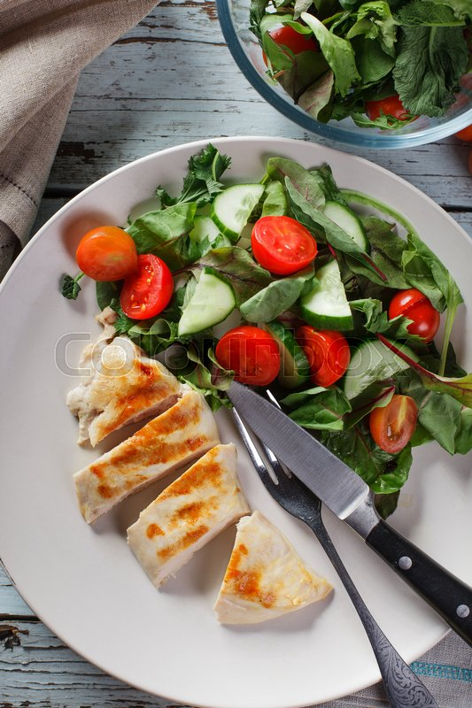 Stock image of 'Cutted grilled chicken meat with fresh vegetable salad, tomatoes on white plate, top view'