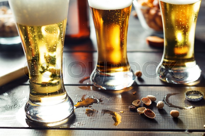 Stock image of 'Three glasses of beer with pistachios on the wooden table'