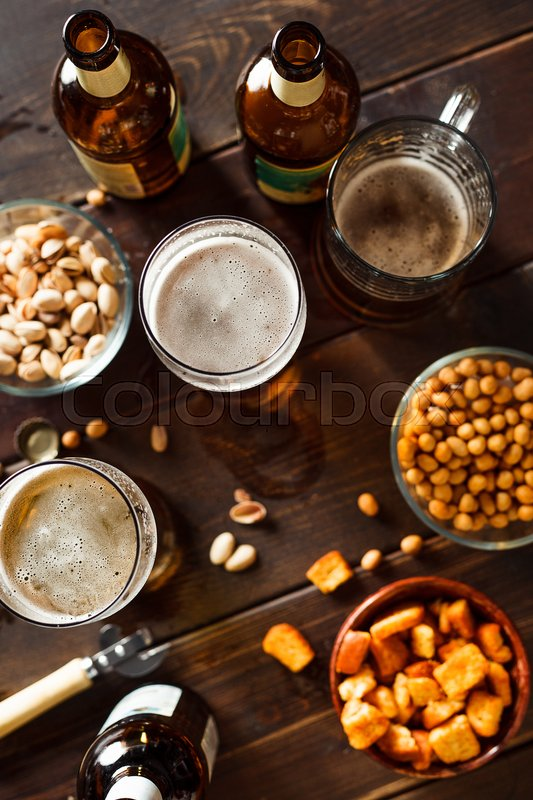 Stock image of 'Overhead view of beer glasses, beer dottkes and snacks on wooden table. Focus on beer'