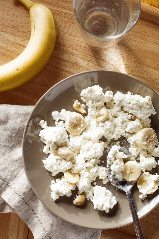 Stock image of 'Overview of plate of cottage cheese with banana and nuts'