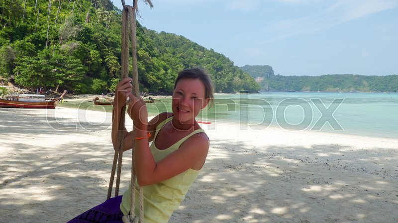 Stock image of 'Girl sitting on a swing at beach with seaview'