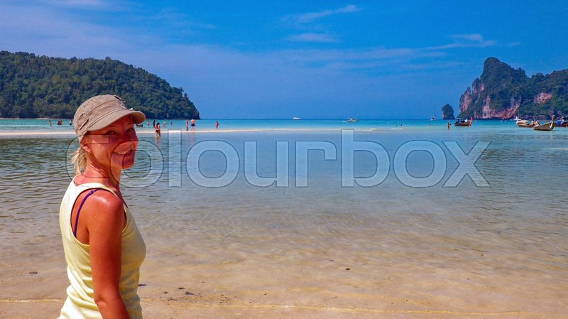 Stock image of 'Young woman enjoying the view on the beach in a lagoon of phi-phi Island, Thailand.'
