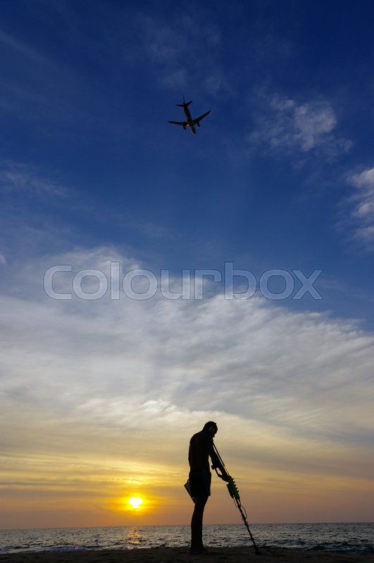 Stock image of 'a treasure hunter with Metal detector on sunset on the beach, with a plan in the sky.'