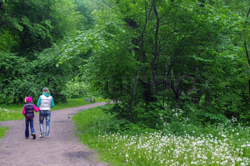 Stock image of 'a mother and daughter walking in the forest and holding hands'