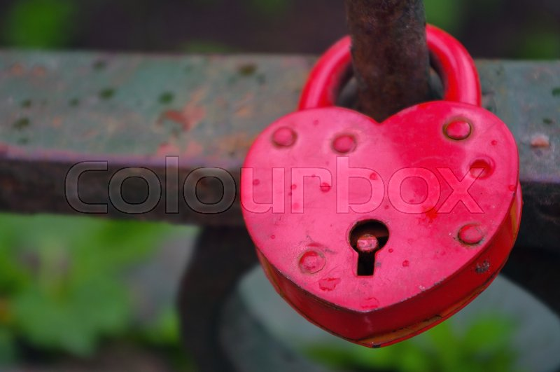 Stock image of 'Beautiful red heart-shaped padlock locked on iron chain'