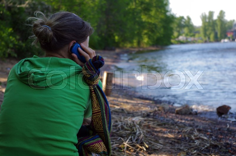 Stock image of 'a modern woman having mobile phone conversation while sitting on a pier near river background with. female talking on her cellphone while relaxing outside'