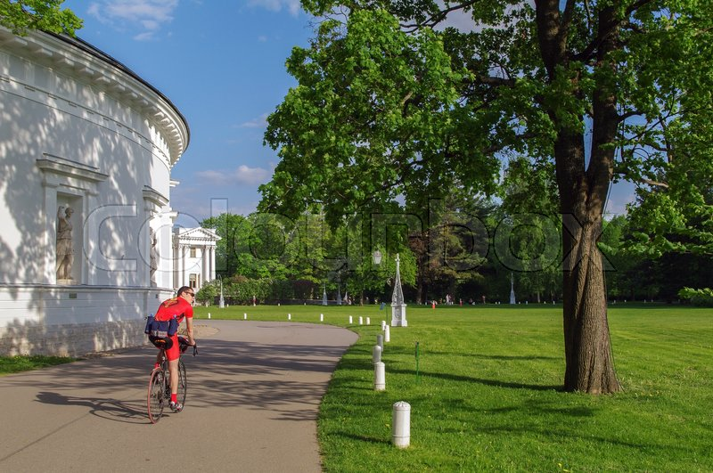 Editorial image of 'a back view of man riding a bicycle. bicyclist on bike in Yelagin park and palace, Saint-Petersburg, Russia'