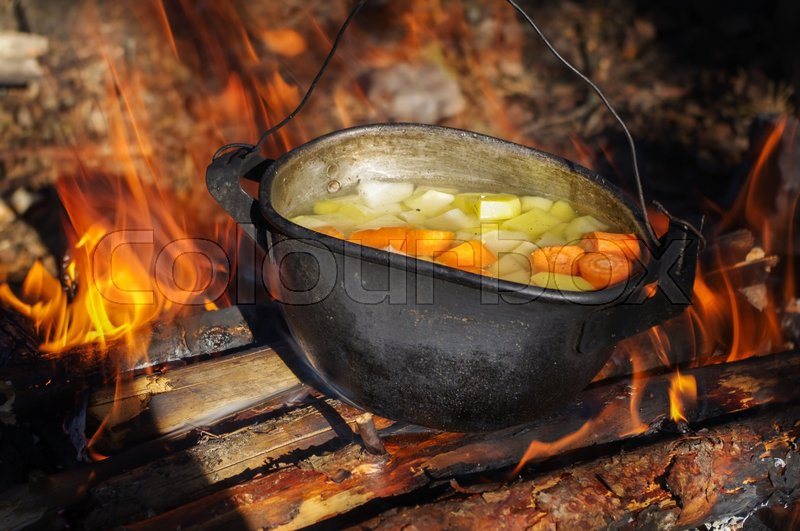 Stock image of 'vegetable soup in old tourist pot at fire place Summer trekking activity'