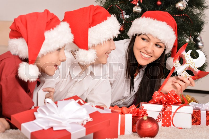Stock image of 'Cute mom and her kids in santa hats with gifts'