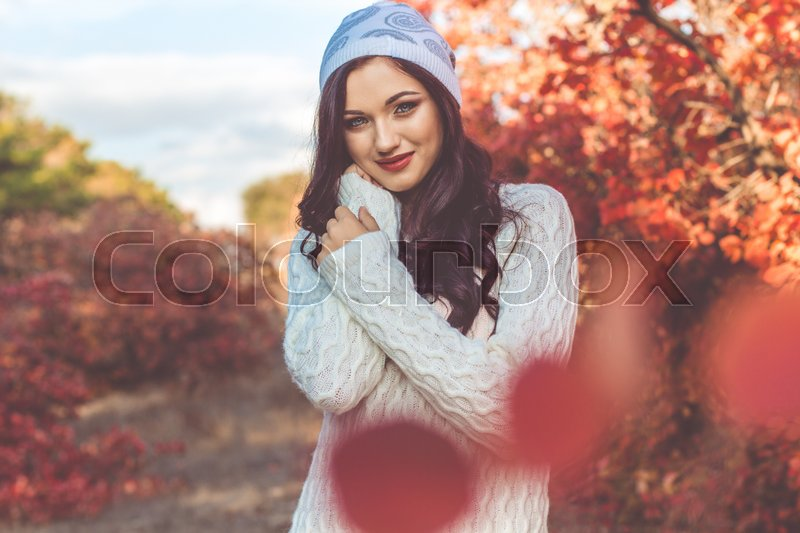 Stock image of 'Beautiful pretty smiling girl with fashion makeup and flawness skin is wearing white warm sweater and winter hat in colorful autumn foliage'
