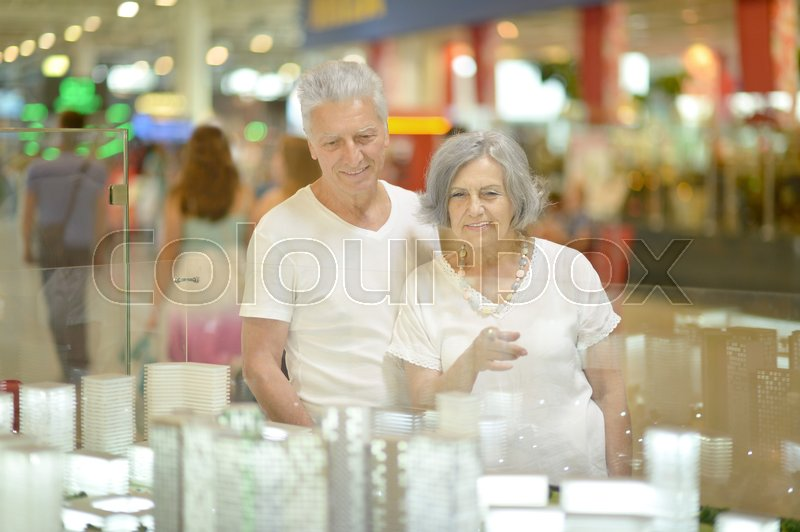 Stock image of 'Portrait of beautiful elderly couple in shopping mall'