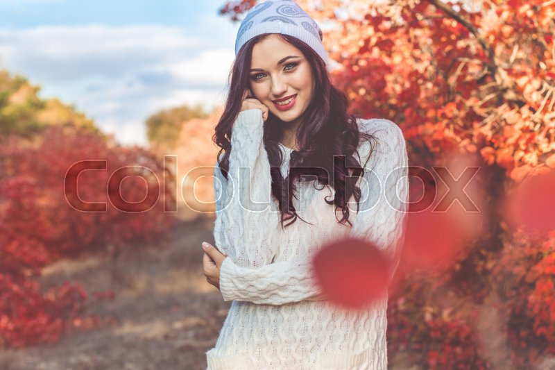 Stock image of 'Beautiful pretty smiling girl with fashion makeup and flawness skin is wearing white warm sweater and winter hat in colorful autumn leaves'