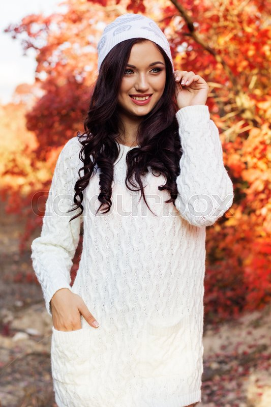 Stock image of 'Beautiful pretty smiling girl with fashion makeup and flawness skin is wearing white warm sweater and winter hat in colorful autumn park'
