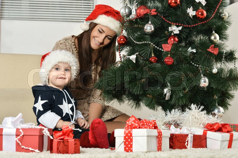 Stock image of 'Happy mother with a little boy near a Christmas tree. new year gifts'