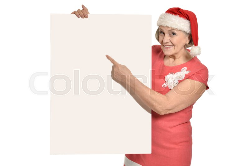Stock image of 'Senior woman in Santa Claus cap holding white blank'