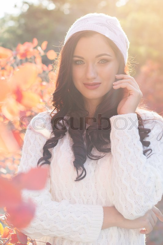 Stock image of 'Portrait of beautiful pretty smiling girl with fashion makeup and flawness skin is wearing white warm sweater and hat in autumn park in sunset lights'