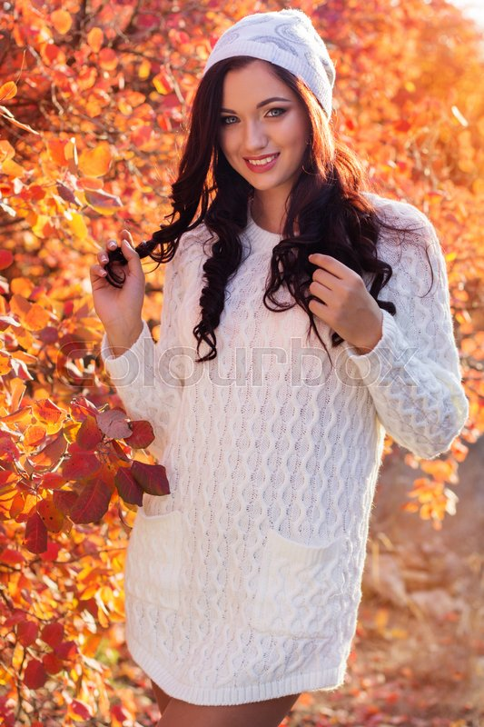 Stock image of 'Portrait of beautiful pretty smiling girl with fashion makeup and flawness skin is wearing white warm sweater and hat in autumn park'