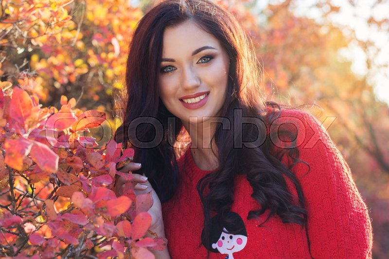Stock image of 'Portrait of beautiful pretty smiling girl with fashion makeup and flawness skin is wearing red sweater in autumn colorful leaves'