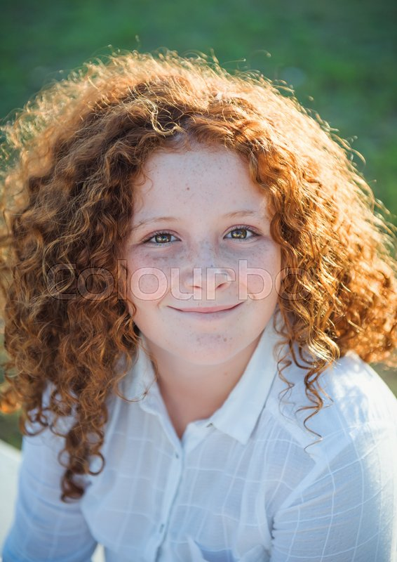 Stock image of 'Redheaded beautiful girl on a background of nature'