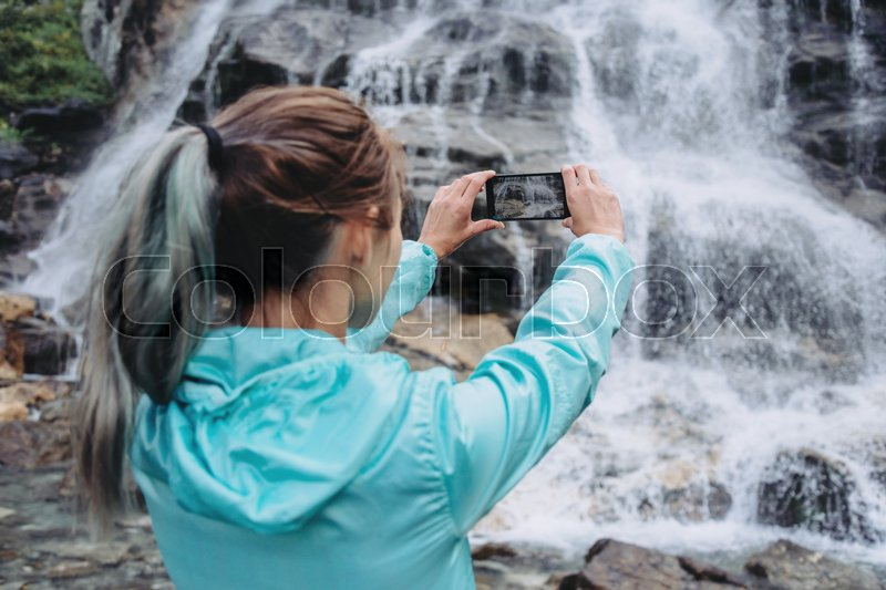 Stock image of 'Traveler young woman photographing with smartphone the waterfall outdoor'
