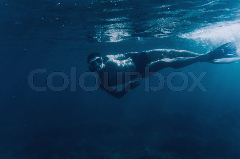 Stock image of 'Young man free diver swimming underwater in blue deep sea, looking at camera'
