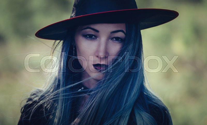 Stock image of 'Portrait of beautiful young woman with dark gothic make-up, looking at camera. Halloween witch'