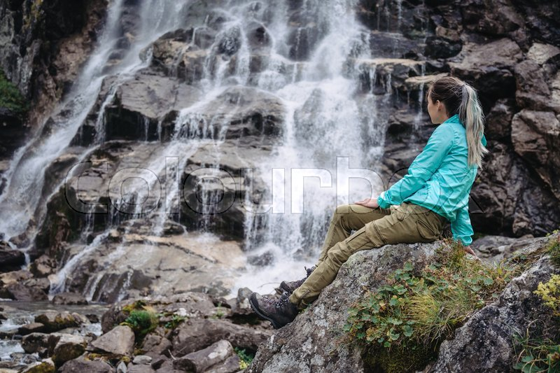 Stock image of 'Traveler young woman sitting on stone and enjoying view of waterfall outdoor'