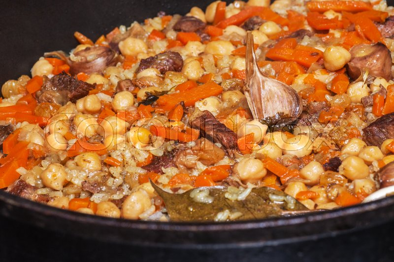 Stock image of 'Pilaf cooked on the grill over a fire. The dish is a large metal bowl. '