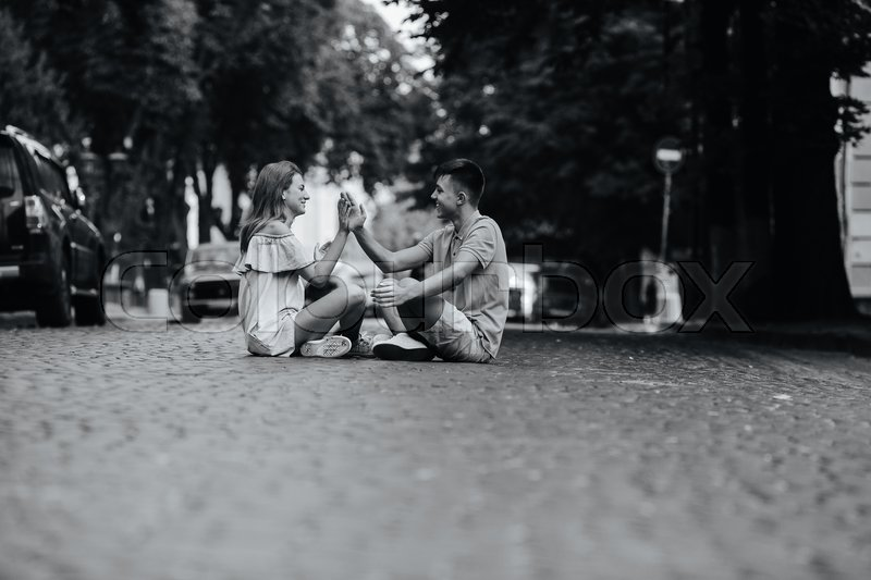 Stock image of 'Young stylish couple sitting on in old town at pavement square'