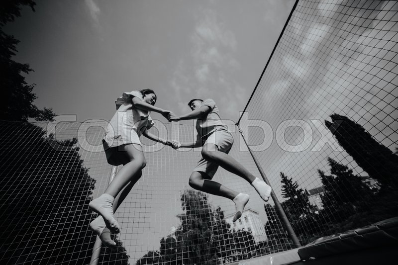 Stock image of 'Full length of a happy couple jumping on trampoline in the park'