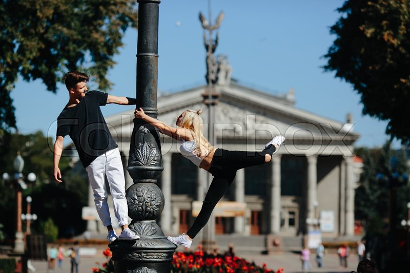 Stock image of 'man and woman performing acrobatic tricks on the street'