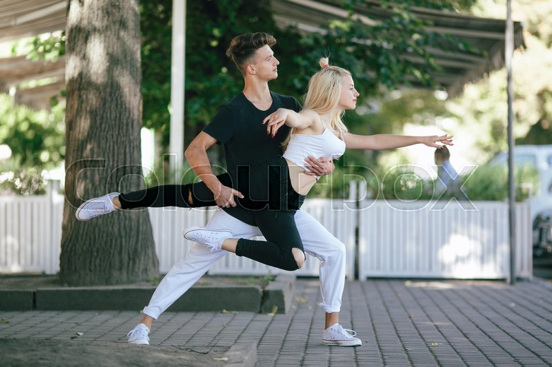 Stock image of 'man and woman dancing in a park on the camera'