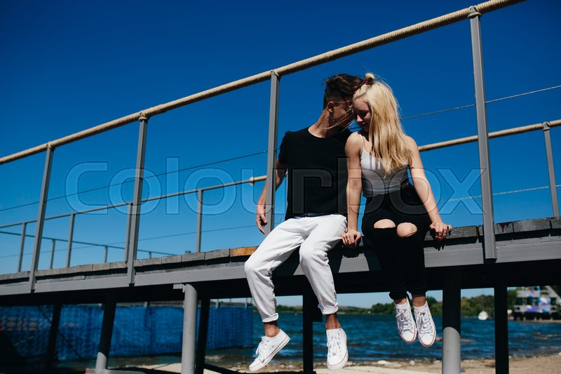 Stock image of 'Happy young couple sitting on the pier in the sunny day'