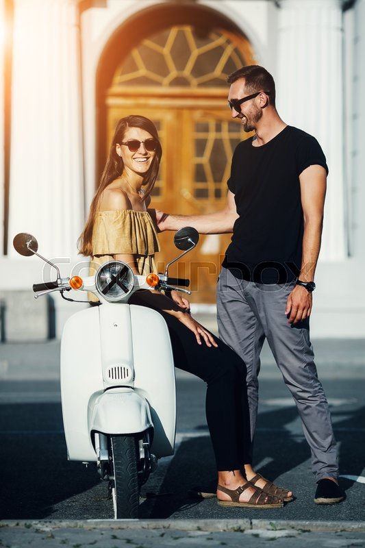 Stock image of 'Cute couple with their scooter on a sunny day in the city'