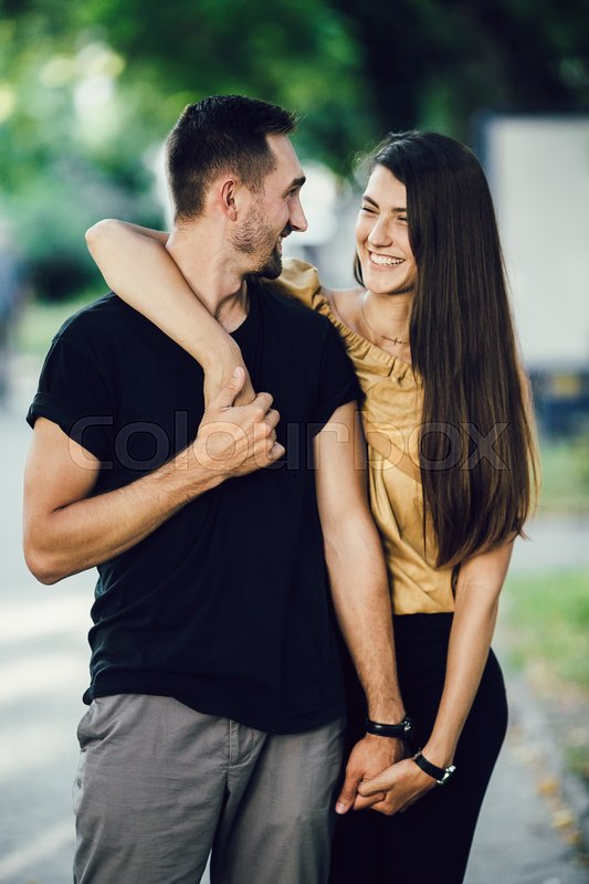 Stock image of 'young man gently hugs the girl in the park'