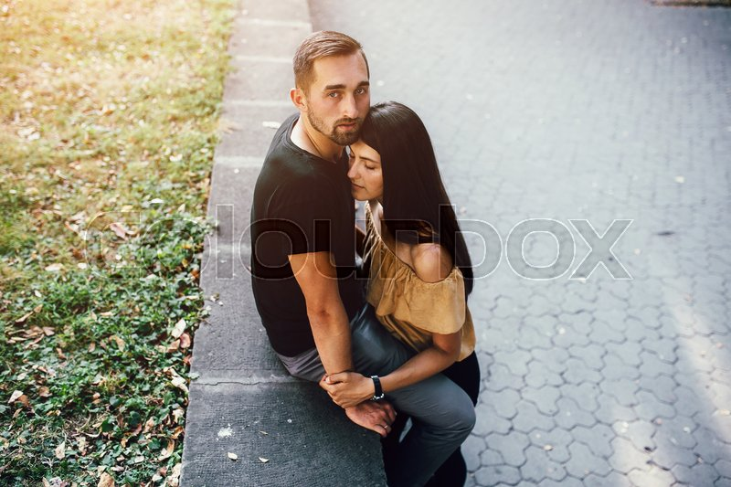 Stock image of 'young man gently hugs girl in the park'