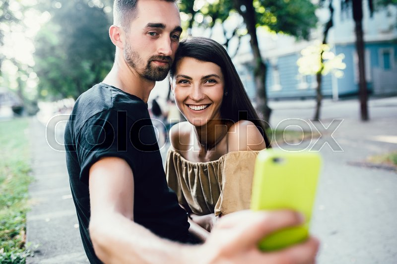 Stock image of 'Beautiful young couple relaxing in the park and makes selfie'