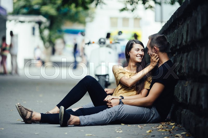 Stock image of 'young beautiful couple sitting on the ground in city near wall'