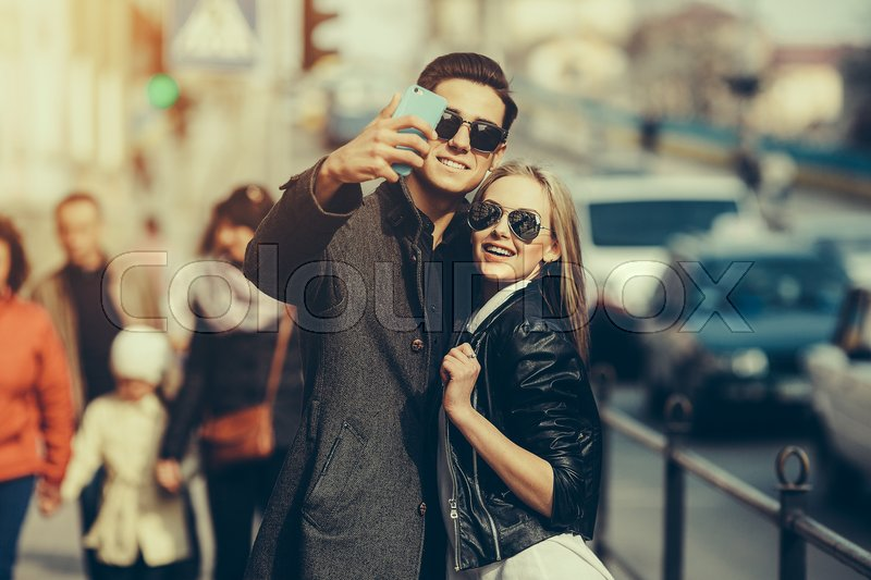 Stock image of 'Photo of a young beautiful couple making selfie on a busy city street'
