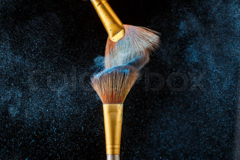 Stock image of 'Two brushes for shadows facing each other with feather shadow on black background'