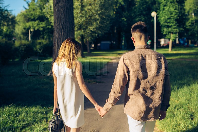 Stock image of 'man and woman walking hand in hand in the park'