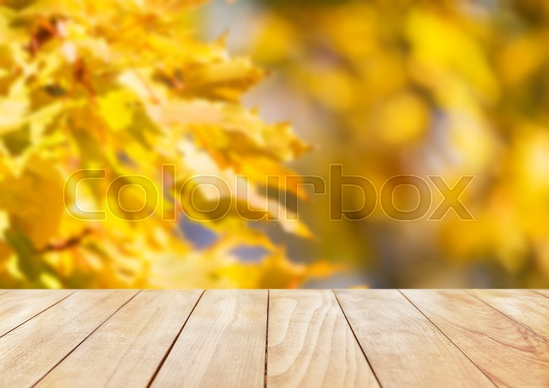 Stock image of 'Yellow wooden desk top with golden leaves, fall background'