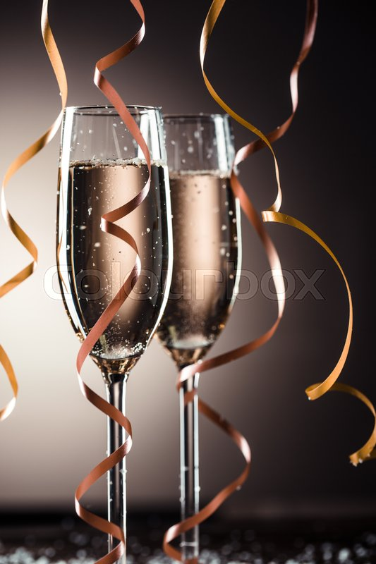 Stock image of 'Stylish image of two champagne glasses and ribbons for decoration flowing from the top'
