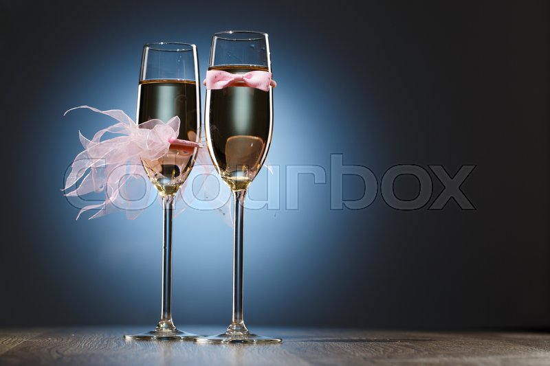 Stock image of 'Two glass of champagne decorated with pink bow-tie of groom and brides veil'