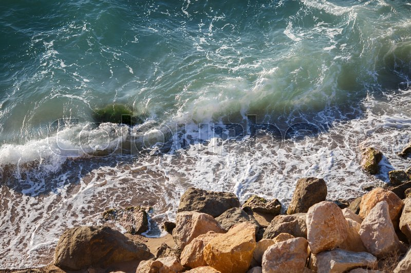 Stock image of 'Beautiful large yellow stones in green waves on sea coast. Scenic view of coastline landscape'