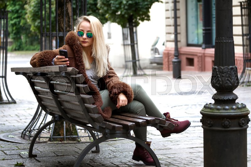 Stock image of 'Young woman sitting on a bench and using a smartphone'