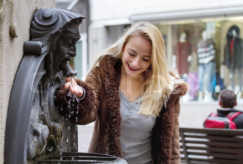 Stock image of 'Young woman drinks water from a fountain'