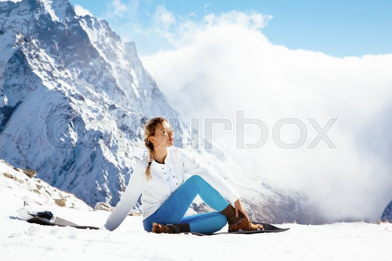 Stock image of 'Young woman practicing yoga pose outdoors in winter. Streching workout in snow on top of mountain. Hiking in cold season. Calm and silent view.'